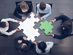 A group of executives work together to solve a puzzle