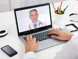 Businessman video-chats with doctor on laptop