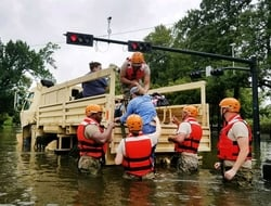 Rescue workers help woman into truck amid floodwaters