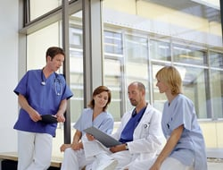 Healthcare workers gathering by a window in a hospital