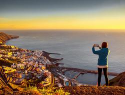Woman taking photo of Santa Cruz on smartphone