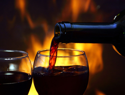 Red wine poured into glasses in front of fireplace