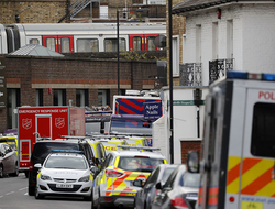 The train, on which a homemade bomb exploded, stands above parked police vehicles on a road below at Parsons Green subway station in London