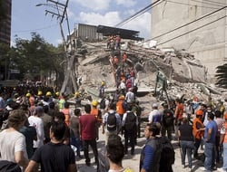 Volunteers and first responders look for survivors in a collapsed building after an earthquake struck Mexico City