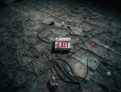 Exit sign on floor amid wreckage