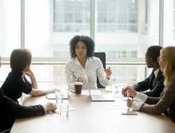People around a conference table headed by a black woman