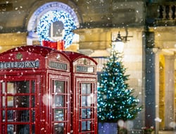 Red telephone booths in front of Christmas decorations lights in London, United Kingdom