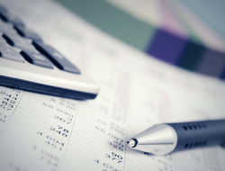 Profits and loss document with calculator and pen