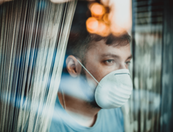 A patient with a surgical mask looks out a window.