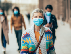 A woman is wearing a face mask on the sidewalk