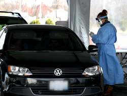 healthcare worker in protective gear prepares to test a driver in a car at a drive-through COVID testing site