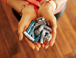Closeup of variety of batteries held by woman