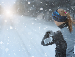 Runner wearing smart phone and watch in snowy conditions