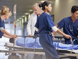 Doctor and nurses wheeling patient in gurney through hospital corridor