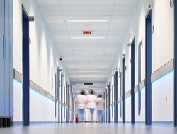 Three nurses walking down a hospital corridor