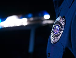 Closeup of police officer's badge with car in background