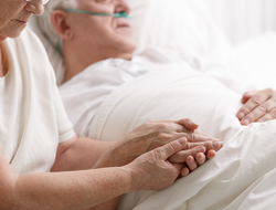Close up of senior woman holding senior man's hand at his bedside in a hospital setting
