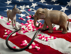 Donkey and elephant figurines face each other with stethoscope and pills with American flag in background