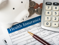 Health insurance form with wood pen, basic calculator, white piggy bank, and pile of coins