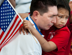 Father and daughter with concerned looks on their faces; the father is holding the daughter and the girl is holding an American flag