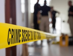 Crime scene tape in a building with blurred forensic team in background