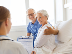 Doctor talking to senior patient and her husband