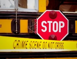 "The side of a school bus with cordon tape that reads ""CRIME SCENE DO NOT CROSS"""