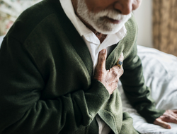 photo of elderly man having heart problems holding his chest