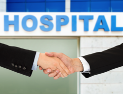 Photo of two men shaking hands in front of a hospital