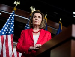 An image of Nancy Pelosi standing at a podium wearing a red blazer.