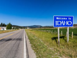"A sign next to a road reading ""Welcome to Idaho"""