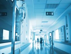 A photo of a hospital hallway and an IV bag