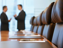 Two blurred executives talk in a conference room