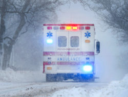 An ambulance drives through winter weather