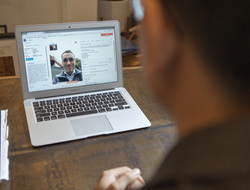 A doctor sits at a desk and a laptop screen shows a patient interacting with the doctor through a virtual visit