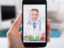 Close-up of video conference with smiling male doctor on smartphone