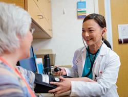 Nurse putting blood pressure cuff on older woman's arm at a CVS MinuteClinic