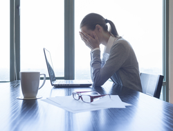 A woman at a desk feeling stress at work