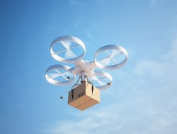 A drone mid-flight delivering a package