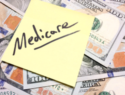 A sticky note says Medicare on top of a pile of money