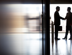 Two businessmen shaking hands in a hallway