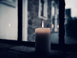 Candle in clear glass window with street in background