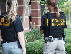 shows the backs of two female enforcement officers with Police HHS/OIG insignia