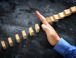 Hand stopping the domino effect
