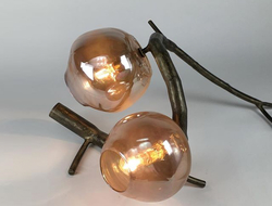 Pod – which is comprised of antique-brass-finished aluminum with handblown recycled bottle glass – resembles a luminescent pupae sprouting forth from the branches of a vine or tree.