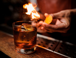 Bartender flaming an orange peel over a cocktail