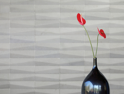 The tapering trapezoid relief dances across the wall surface, creating shadows while remaining contemporary and clean.