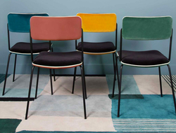 Bearing clean lines, the Double Jeu chair has a steel frame and uses black Italian velvet and white piping.