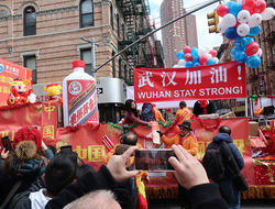 People display signs in support of Wuhan, China, at the center of the coronavirus outbreak, during the Lunar New Year parade, Sunday, Feb. 9, 2020, in Manhattan's Chinatown, in New York.