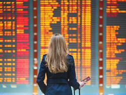 woman at airport looking at information board